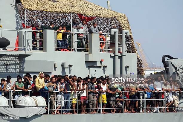 Migrants stand on the Irish military vessel Naimh as it arrives in the port of Palermo on August 6 with 367 survivors aboard and 25 coffins after...