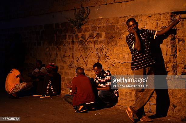 Migrants stand outside 'Baobab' migration centre next to the Tiburtina train station in Rome on June 13 2015 Hundreds of migrants mainly from...