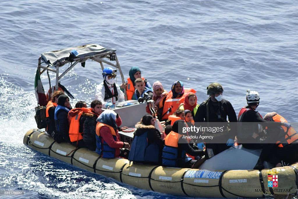 Migrants stands in a boat as Bettica and Bergamini ships of Italian Navy rescue migrants from an overcrowded boat which was about to capsize at Sicilian Strait, between Libya and Italy, in Mediterranean sea on May 25, 2016. The Italian Navy saved around 500 migrants as they found dead bodies of seven migrants in the sea during the operations.
