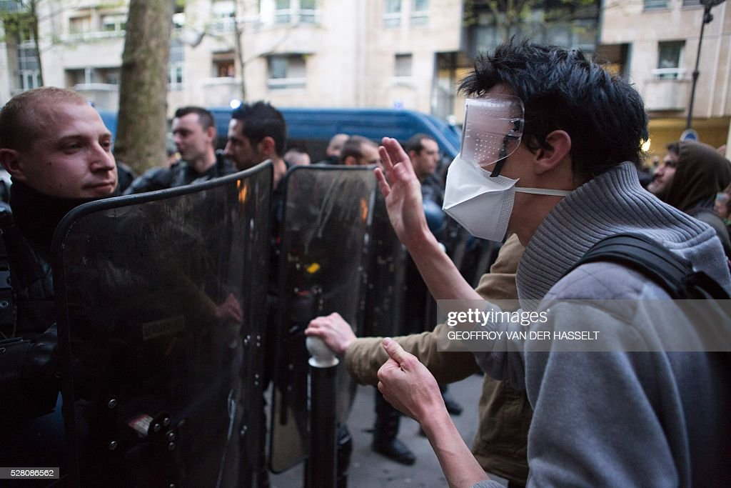 A migrants' supporter faces policemen to protest against the Jean-Jaur��s highschool evacuation in Paris on May 4, 2016. The police evacuated this morning a highschool under construction occupied by 200 migrants in northeatern Paris since two weeks, while protesters clashed with policemen outside the building. / AFP / GEOFFROY