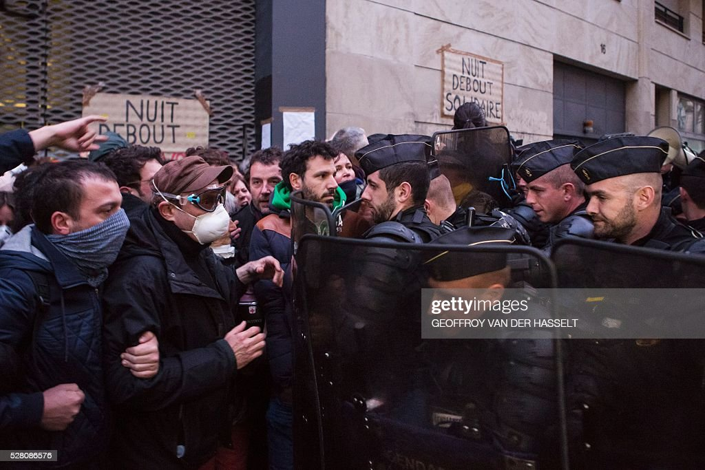 Migrants' supporters clashes with anti-riot policemen to protest against the Jean-Jaur��s highschool evacuation by the police in Paris on May 4, 2016. The police evacuated this morning a highschool under construction occupied by 200 migrants in northeatern Paris since two weeks, while protesters clashed with policemen outside the building. / AFP / GEOFFROY