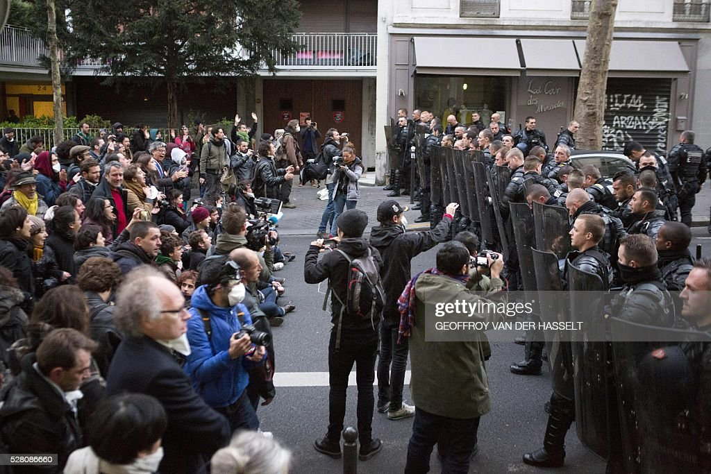 Migrants' supporters face anti-riot policemen to protest against the Jean-Jaur��s highschool evacuation in Paris on May 4, 2016. The police evacuated this morning a highschool under construction occupied by 200 migrants in northeatern Paris since two weeks, while protesters clashed with policemen outside the building. / AFP / GEOFFROY
