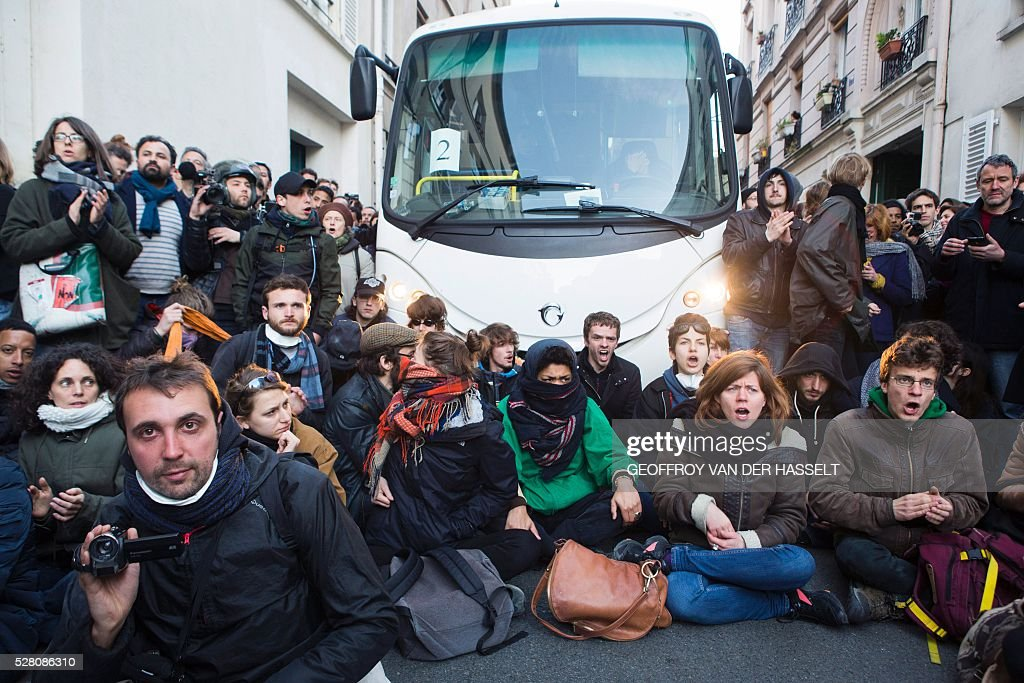 Migrants' supporters sit in the street to protest against the Jean-Jaur��s highschool evacuation by the police in Paris on May 4, 2016. The police evacuated this morning a highschool under construction occupied by 200 migrants in northeatern Paris since two weeks, while protesters clashed with policemen outside the building. / AFP / GEOFFROY
