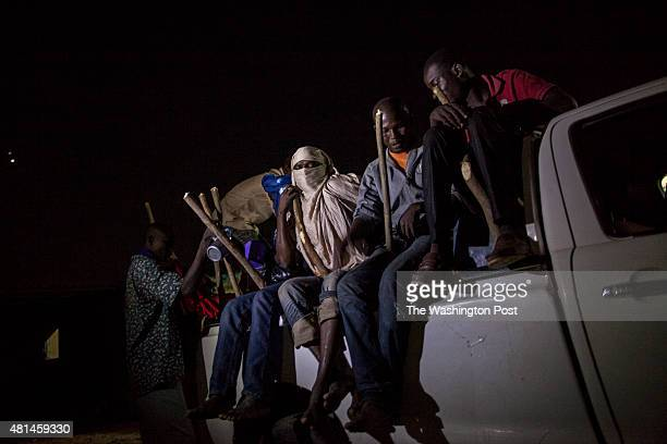 AGADEZ NIGER Migrants take their positions on the back of a Toyota pickup truck loaded with water provisions and fuel Wooden stakes were lodged...