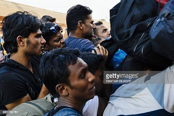 Migrants try to climb onto a train heading to the border with Serbia at the train station of Gevgelija on the MacedonianGreek border on August 12...