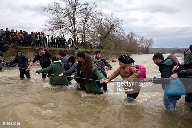 Migrants try to cross a river after leaving the Idomeni refugee camp on March 13 2016 in Idomeni Greece The decision by Macedonia to close its border...