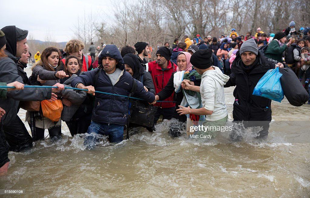 Migrants try to cross a river after leaving the Idomeni refugee camp, on March 14, 2016 in Idomeni, Greece. The decision by Macedonia to close its border to migrants on Wednesday has left thousands of people stranded at the Greek transit camp. The closure, following the lead taken by neighbouring countries, has effectively sealed the so-called western Balkan route, the main migration route that has been used by hundreds of thousands of migrants to reach countries in western Europe such as Germany. Humanitarian workers have described the conditions at the camp as desperate, which has been made much worse by recent bouts of heavy rain.