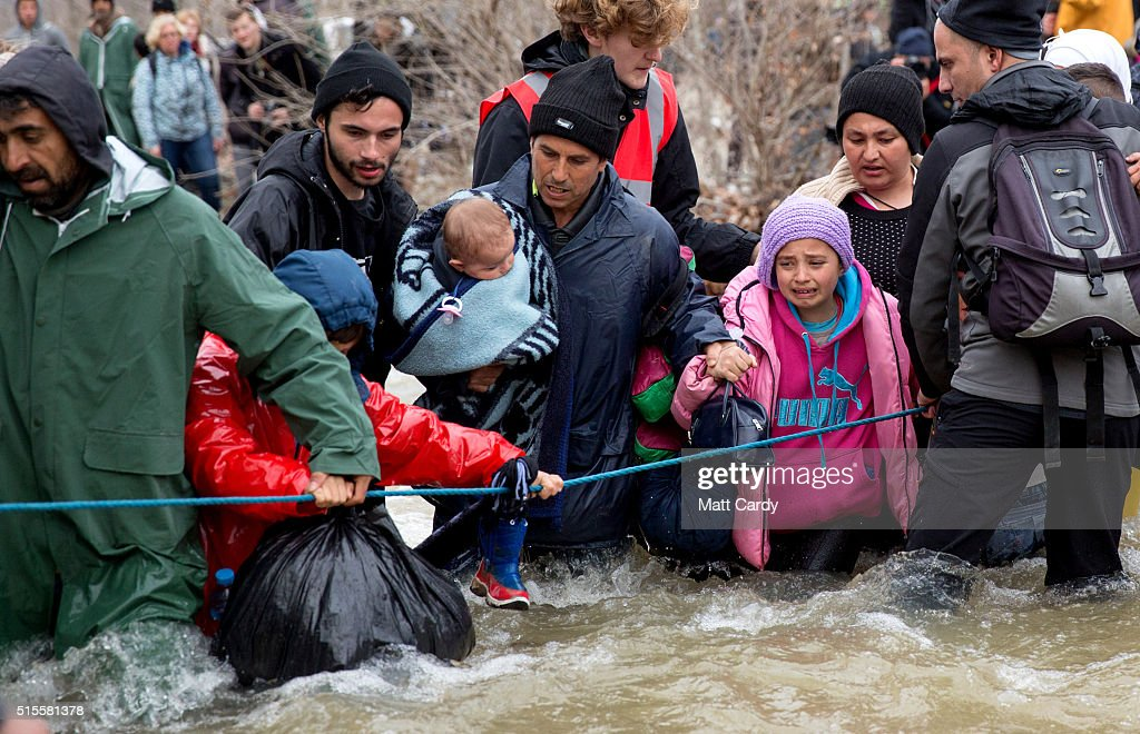 Migrants try to cross the river after leaving the Idomeni refugee camp on March 13, 2016 in Idomeni, Greece. The decision by Macedonia to close its border to migrants on Wednesday has left thousands of people stranded at the Greek transit camp. The closure, following the lead taken by neighbouring countries, has effectively sealed the so-called western Balkan route, the main migration route that has been used by hundreds of thousands of migrants to reach countries in western Europe such as Germany. Humanitarian workers have described the conditions at the camp as desperate, which has been made much worse by recent bouts of heavy rain.