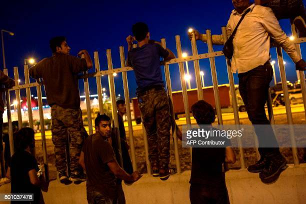 TOPSHOT Migrants try to jump over a fence into a ferry terminal in Patras southwestern Greece on June 20 2017 Khalid a 13yearold from Afghanistan...