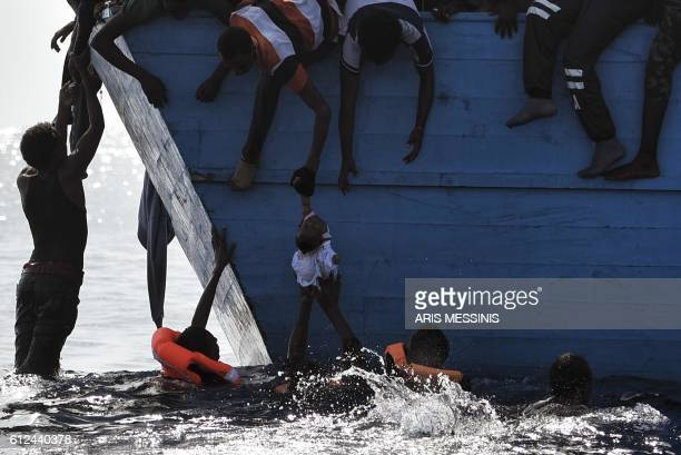 TOPSHOT Migrants try to pull a child out of the water as they wait to be rescued by members of Proactiva Open Arms NGO in the Mediterranean sea some...