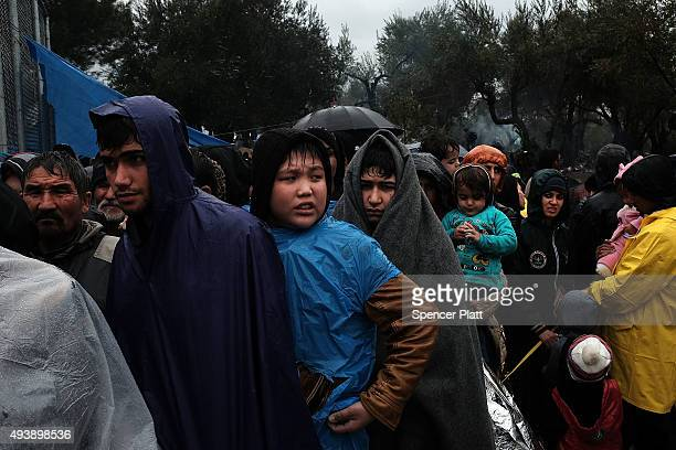 Migrants try to stay dry and warm at the increasingly overwhelmed Moria camp on the island of Lesbos on October 23 2015 in Mitilini Greece Dozens of...
