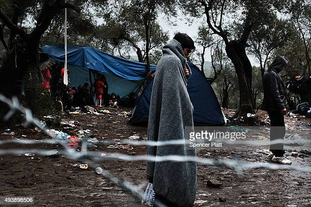 Migrants try to stay warm at the increasingly overwhelmed Moria camp on the island of Lesbos on October 23 2015 in Mitilini Greece Dozens of rafts...