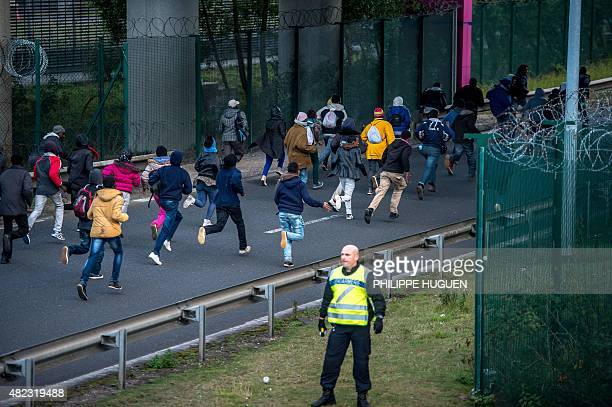 Migrants trying to reach the Channel Tunnel run past a policeman on the Eurotunnel site in Coquelles near Calais northern France on late July 29 2015...