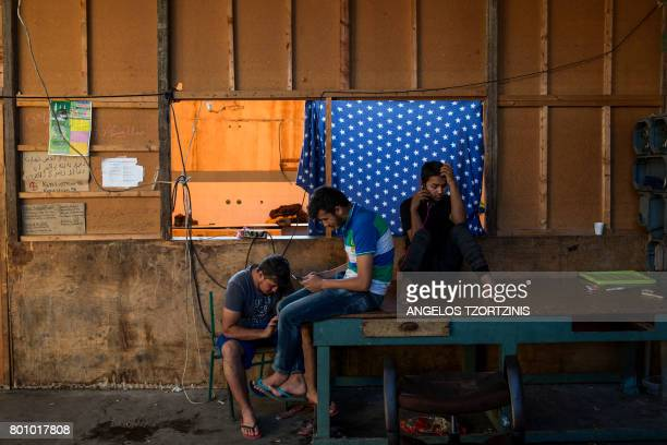 TOPSHOT Migrants use their mobile phones at an abandoned factory which has been their temporary home in Patras southwestern Greece on June 20 2017...