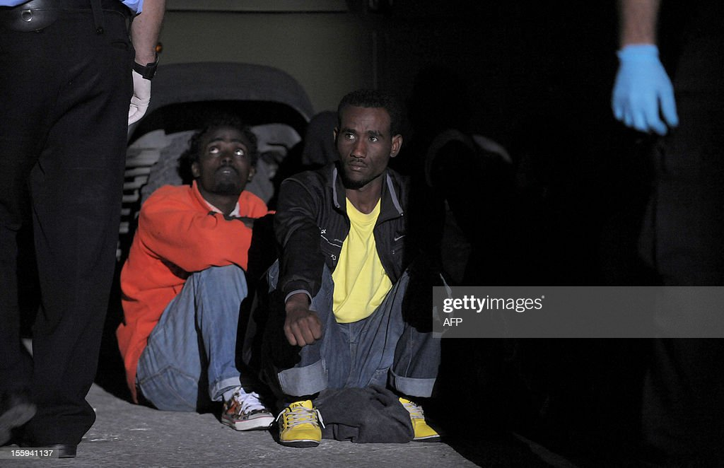 Migrants wait after disembarking from a patrol boat after being rescued from their vessel early on November 9, 2012 in Valletta. The Maltese military rescued 250 undocumented migrants believed to be Eritrean from a stricken boat, officials said, after reports the vessel had been adrift for days. AFP PHOTO/Matthew Mirabelli -MALTA OUT-