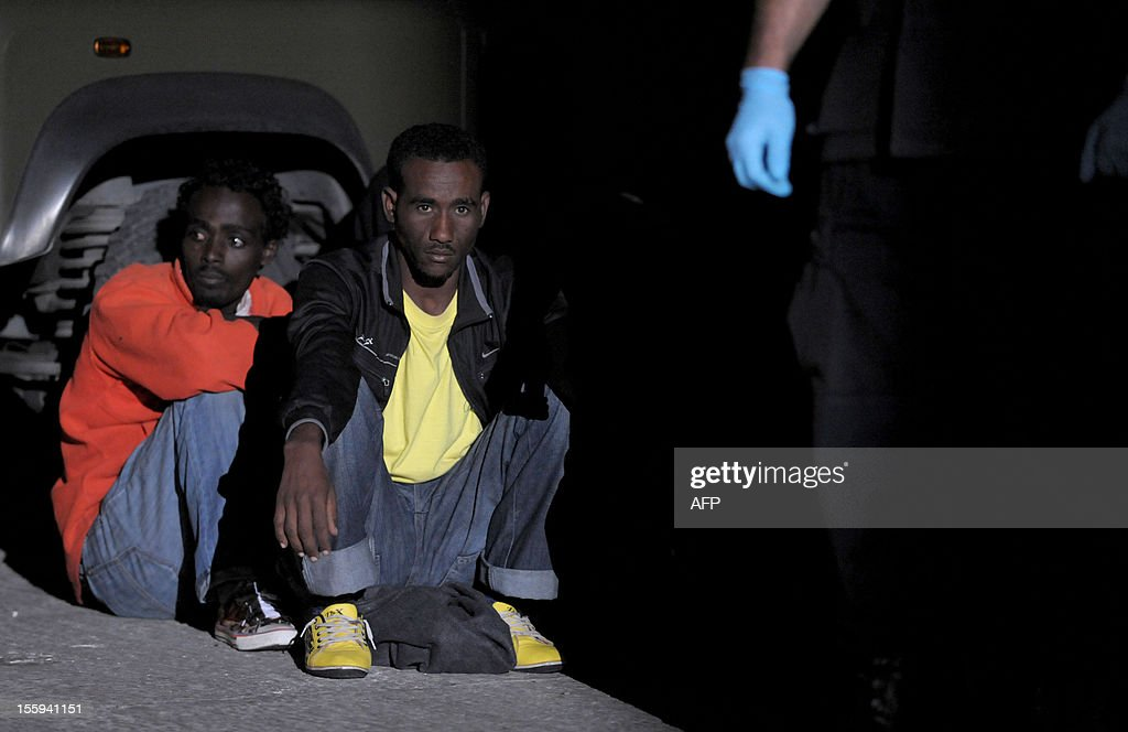 Migrants wait after disembarking from a patrol boat after being rescued from their vessel early on November 9, 2012 in Valletta. The Maltese military rescued 250 undocumented migrants believed to be Eritrean from a stricken boat, officials said, after reports the vessel had been adrift for days. AFP PHOTO/Matthew Mirabelli -MALTA