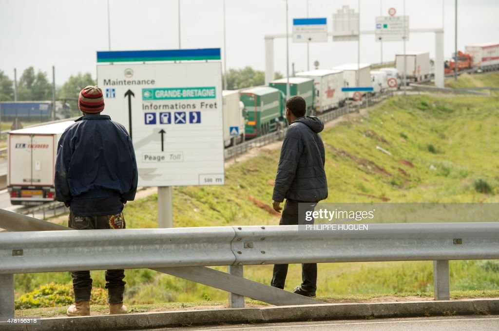 Migrants wait along the A16 highway as they try to access the Channel Tunnel on June 23, 2015 in Calais, northern France.