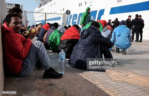 Migrants wait at the port of Lampedusa to board a ferry bound for Porto Empedocle in Sicily on February 20 2015 Authorities on the Italian island of...
