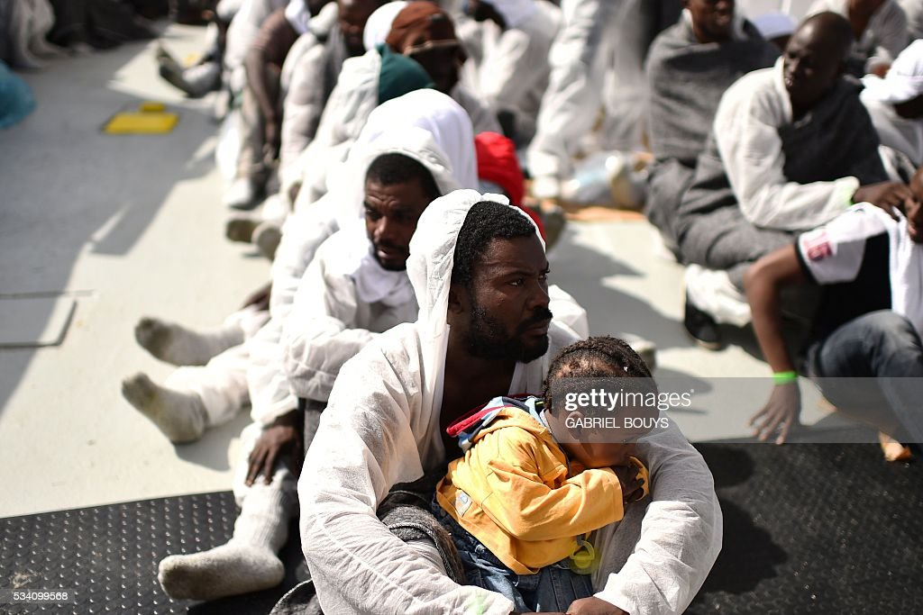 Migrants wait for a meal aboard the rescue ship 'Aquarius', on May 25, 2016 a day after a rescue operation of migrants and refugees off the Libyan coast. The Aquarius is a former North Atlantic fisheries protection ship now used by humanitarians SOS Mediterranee and Medecins Sans Frontieres (Doctors without Borders) which patrols to rescue migrants and refugees trying to reach Europe crossing the Mediterranean sea aboard rubber boats or old fishing boat. / AFP / GABRIEL