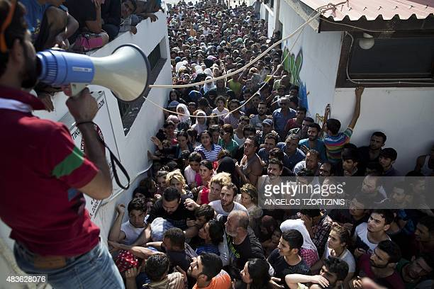 Migrants wait for a registration procedure at the stadium on the Greek island of Kos on August 11 2015 Police on the Greek island on Kos hit migrants...