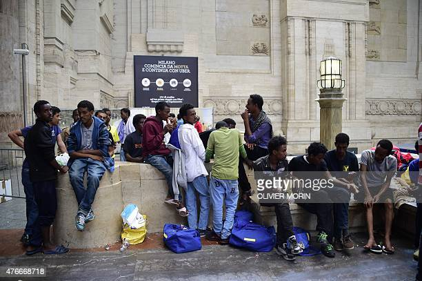 Migrants wait for food at the Milan train station on June 11 as about 300 migrants mainly from Eritrea arrived in Milan late on June 10 and wait to...