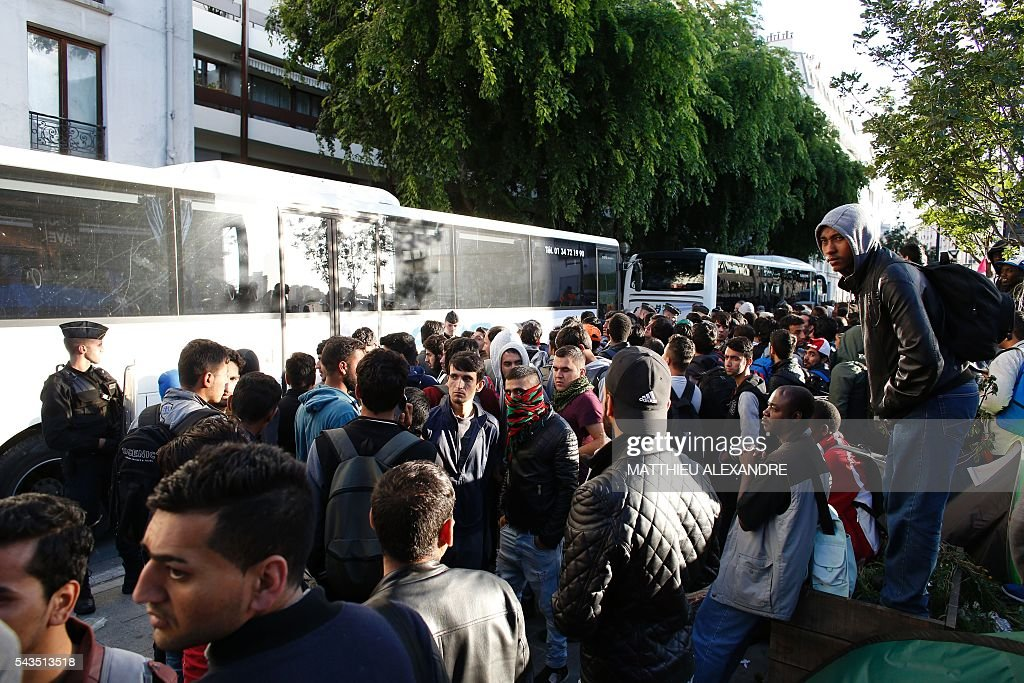 Migrants wait for the French Gendarmes to evacuate their camp on June 29, 2016 in Paris. The police started early on June 29, 2016, the evacuation of several hundreds of migrants, from a camp at the former SNCF Hall 'Pajol'. / AFP / MATTHIEU