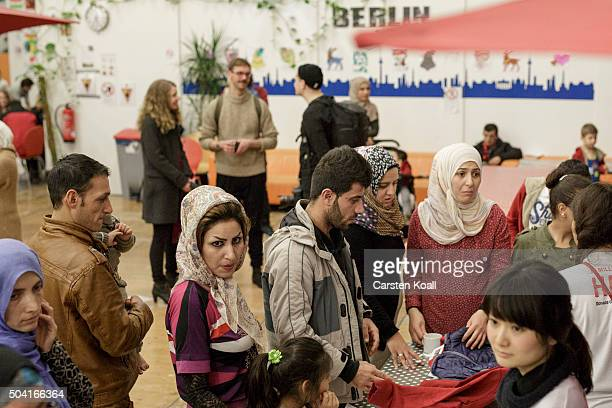 Migrants wait in a line to get clothes donated by Japanese casual clothing company Uniqlo at the Berliner Stadtmission on January 9 2016 in Berlin...