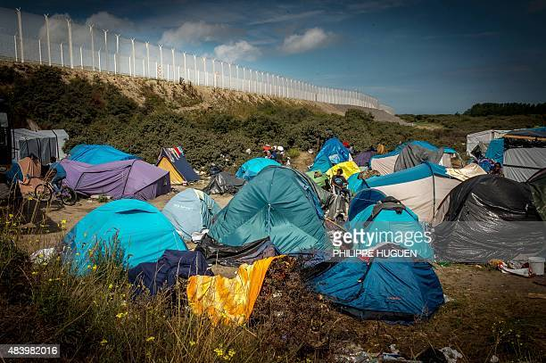 Migrants wait in a migrant camp called 'New Jungle' next to the fence of the ferry port in Calais northern France on August 14 2015 Some 3000...