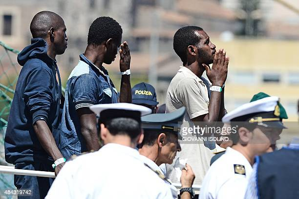 Migrants wait in line as they disembark from the Norwegian military ship Siem Pilot in the Italian port of Catina on August 17 2015 At least 49...