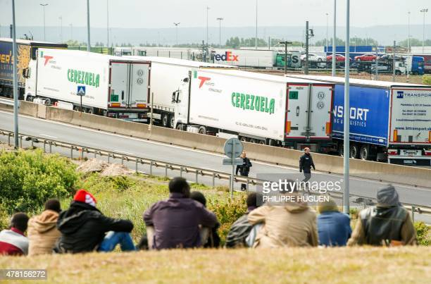 Migrants wait near the A16 highway as they try to access the Channel Tunnel on June 23 2015 in Calais northern France AFP PHOTO PHILIPPE HUGUEN