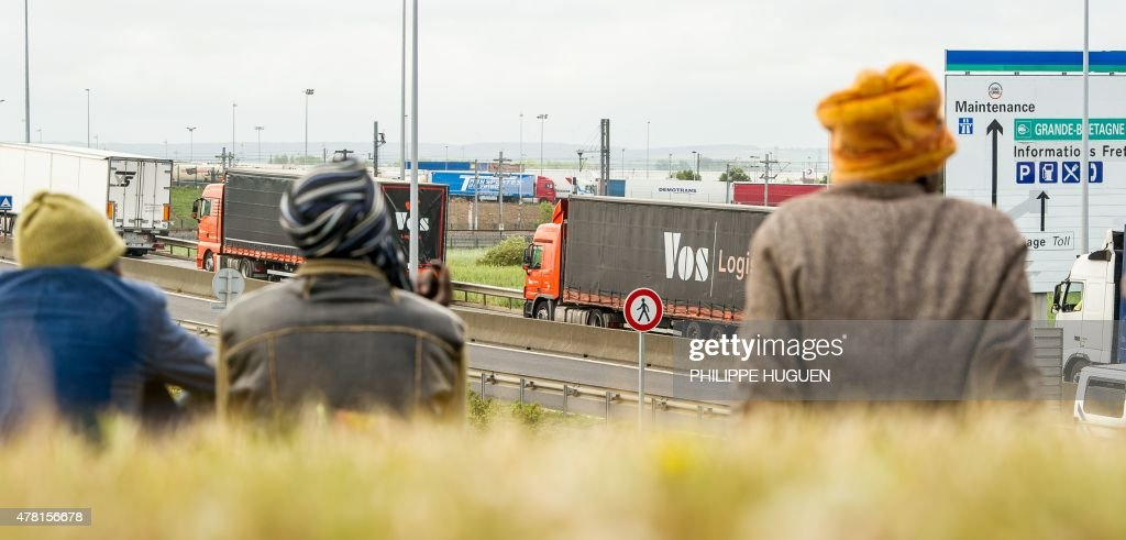 Migrants wait near the A16 highway as they try to access the Channel Tunnel on June 23, 2015 in Calais, northern France.