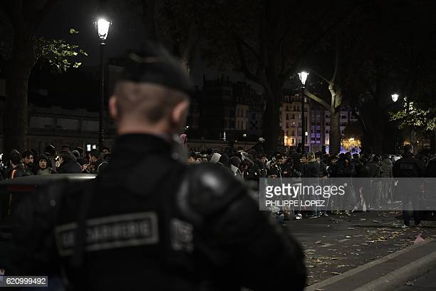 Migrants wait on a road during an evacuation by police of a makeshift camp in Paris on November 4 one of several camps sprouting up around the French...