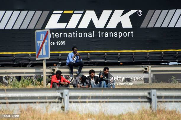Migrants wait on the roadside along the ring road leading to the port of Calais northern France on June 21 2017 A driver died early on June 20 2017...