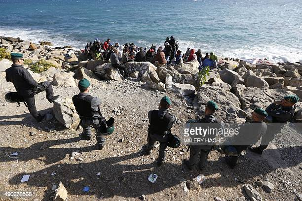 Migrants wait on the rocks on the shoreline under the surveillance of policemen on September 30 2015 at the FrenchItalian border in Ventimiglia The...