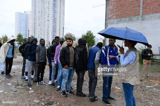 Migrants wait to be evacuated by bus from a makeshift camp at Porte de la Chapelle in the north of Paris on August 18 2017 More than a thousand...