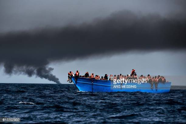 Migrants wait to be rescued as they drift at sunset in the Mediterranean Sea some 20 nautical miles north off the coast of Libya on October 3 2016...
