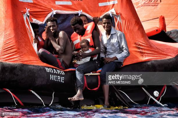 TOPSHOT Migrants wait to be rescued as they drift in the Mediterranean Sea some 20 nautical miles north off the coast of Libya on October 3 2016...
