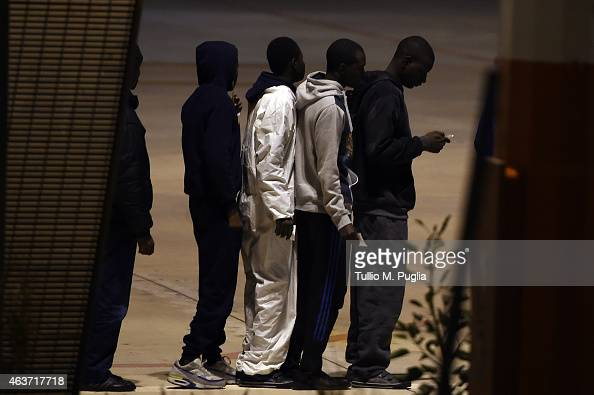 Migrants wait to board a plane at Lampedusa airport bound for a detention center elsewhere in the country on February 17 2015 in Lampedusa Italy...