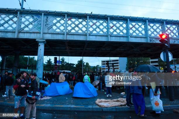 Migrants wait to board buses as French antiriot police force CRS officers prepare the evacuation of a makeshift camp at Porte de la Chapelle in the...