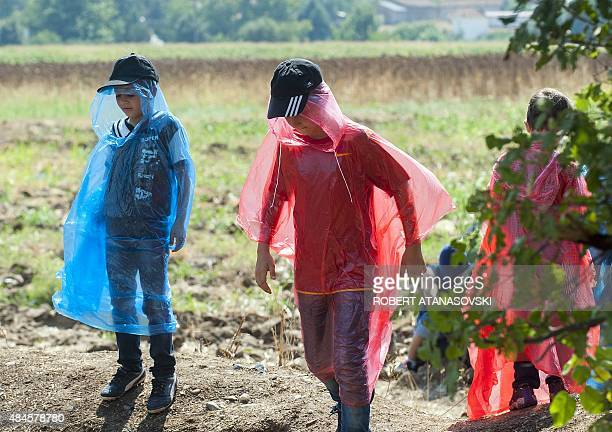 Migrants wait to cross the MacedonianGreek border near the town of Gevgelija on August 20 2015 Macedonian special police forces arrived this morning...