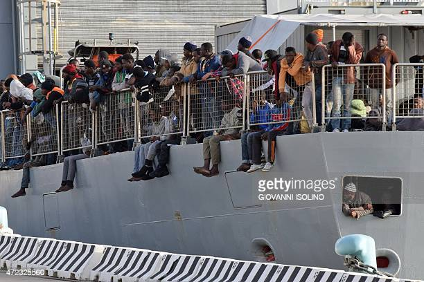 Migrants wait to disembark from a military ship following a rescue operation at sea as part of the Frontexcoordinated Operation Triton on May 6 2015...