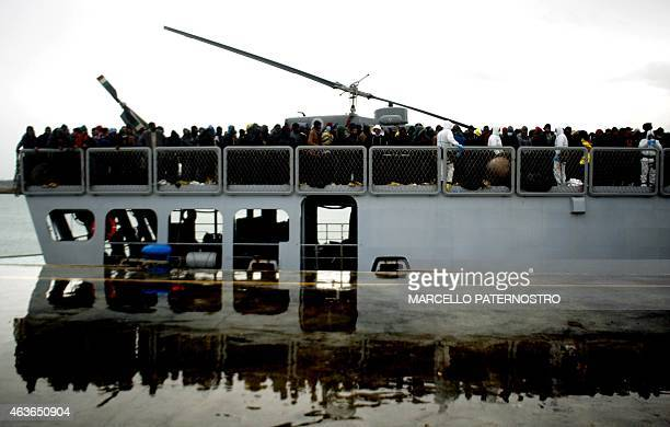 Migrants wait to disembark from a ship on February 17 2015 in the port of Porto Empedocle south Sicily following a rescue operation of migrants as...