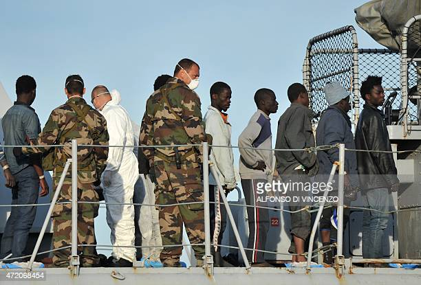 Migrants wait to disembark from French military ship Commandant Birot after being rescued as part of the Frontexcoordinated Operation Triton off the...