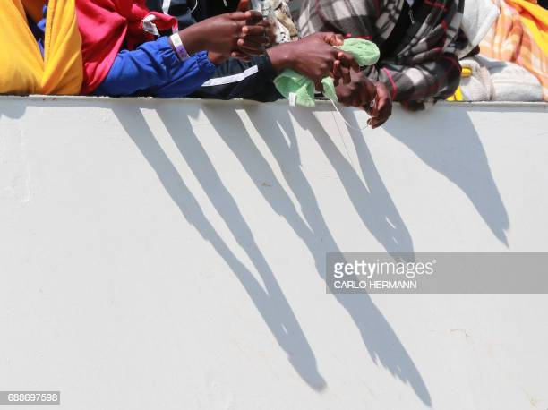 Migrants wait to disembark from the Aquarius rescue Ship run by NGO SOS Mediterranee and Medecins Sans Frontieres in the port of Salerno after a...