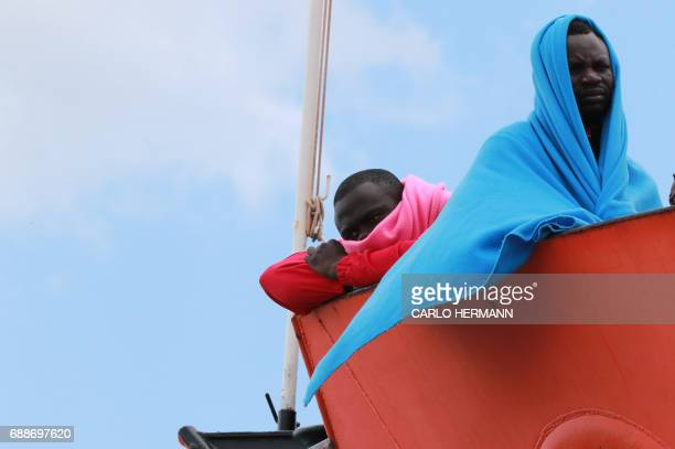 TOPSHOT Migrants wait to disembark from the Aquarius rescue Ship run by NGO SOS Mediterranee and Medecins Sans Frontieres in the port of Salerno...