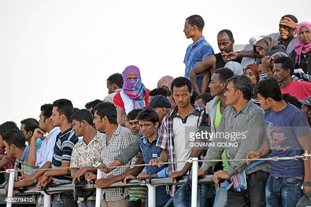 Migrants wait to disembark from the patrol vessel Fiorillo of the Italian Coast Guard after it arrived in the port of Pozzallo on August 7 2015 after...