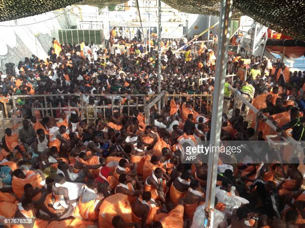 TOPSHOT Migrants wait to disembark from the Siem Pilot ship on October 24 2016 in Palermo after rescue operations of migrants at see during the...