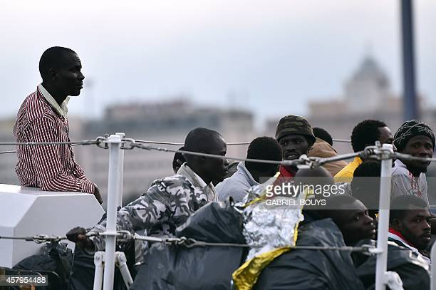 Migrants wait to disembark on October 20 2014 from the 'Fiorillo' coast guard boat in the port of Palermo The memory of terrified parents and...