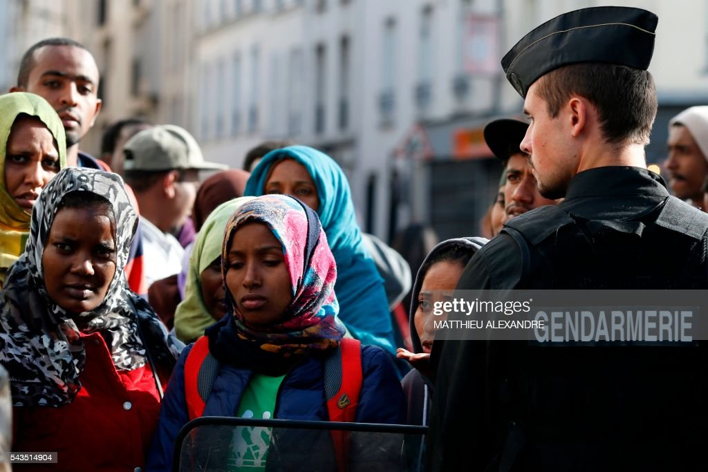 Migrants wait to get into a bus as French Gendarmes evacuate their camp on June 29, 2016 in Paris. The police started early on June 29, 2016, the evacuation of several hundreds of migrants, from a camp at the former SNCF Hall 'Pajol'. / AFP / MATTHIEU