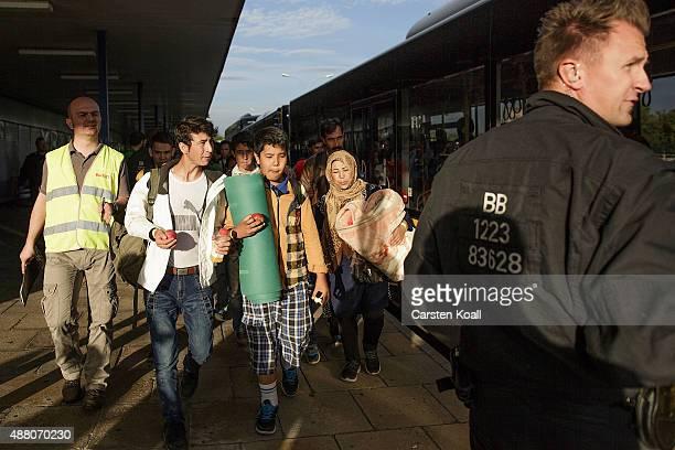 Migrants wait to take a bus after arriving on an ICE highspeed train of Deutsche Bahn from Munich near Berlin on September 13 2015 in Schoenefeld...